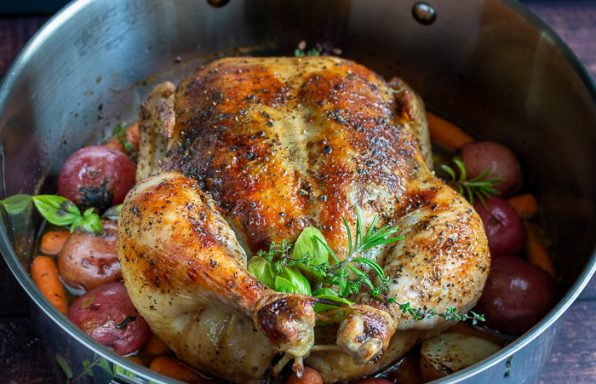 Perfectly roasted whole chicken with crispy skin, fresh herbs surrounded by cooked potatoes and carrots.