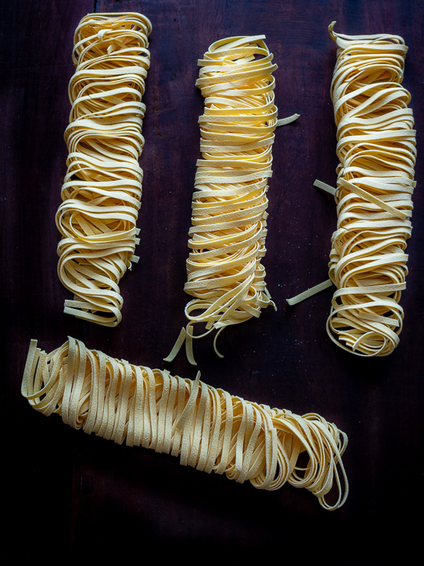 Four dried bundles of dried fettuccine pasta on a dark cutting board.