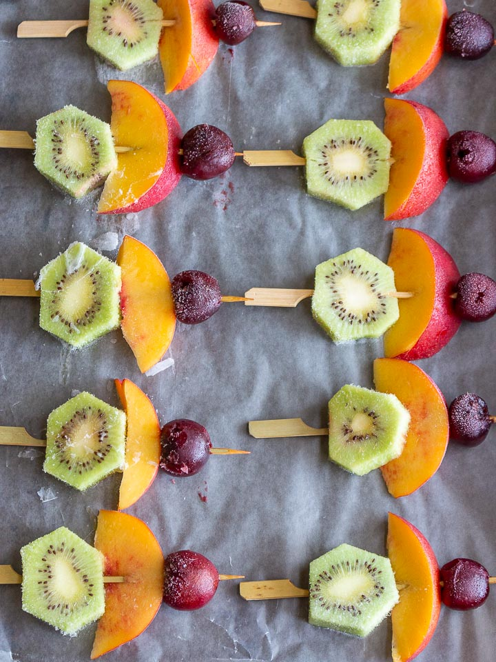 Skewers of kiwi, nectarines and cherries on a baking sheet that have been frozen.
