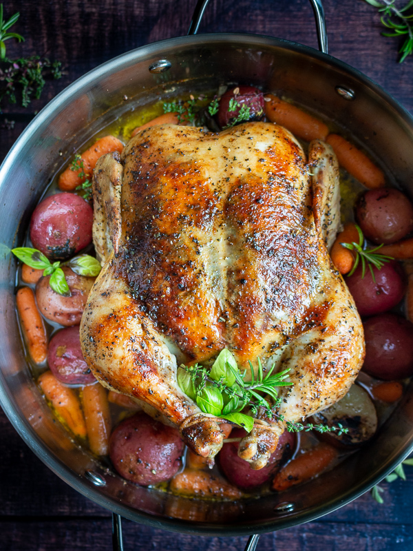 Top Down Shot. Perfectly roasted whole chicken with crispy skin, fresh herbs surrounded by cooked potatoes and carrots.