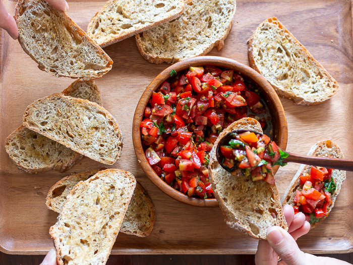 Top down shot showing many friends digging into the shared platter of bruschetta bread.