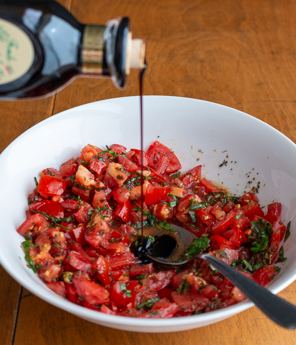 Thick aged balsamic vinegar getting drizzled onto the chopped tomatoes.