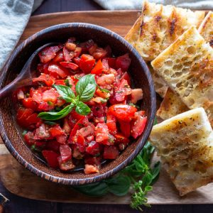 Grilled Italian bread with delicious tomatoes with EVOO and aged balsamic on a wooden platter.