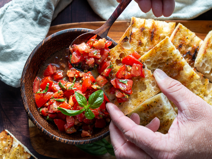 Scooping delicious marinated tomatoes with EVOO and Balsamic onto of crusty grilled bread.