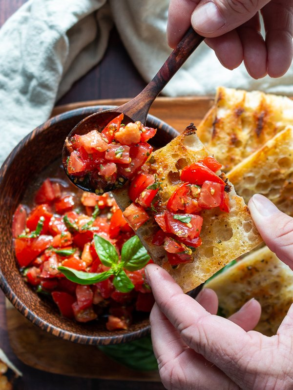 Delicious marinated tomatoes with fresh basil, EVOO and aged balsamic getting scooped on a toasted crostini.