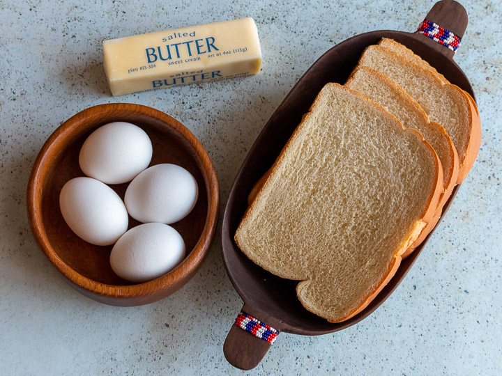 Top down photo of eggs, butter and bread in wooden bowls.