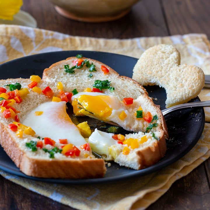 A baked egg in a hole with peppers and parmesan with a drippy egg center.