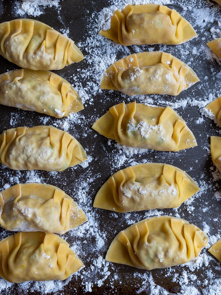 Many prepared dumplings on a baking sheet ready to be cooked.
