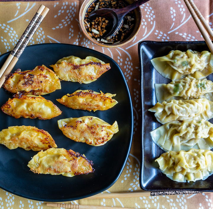 Plate of pan fried and boiled Chinese dumplings on black plates.