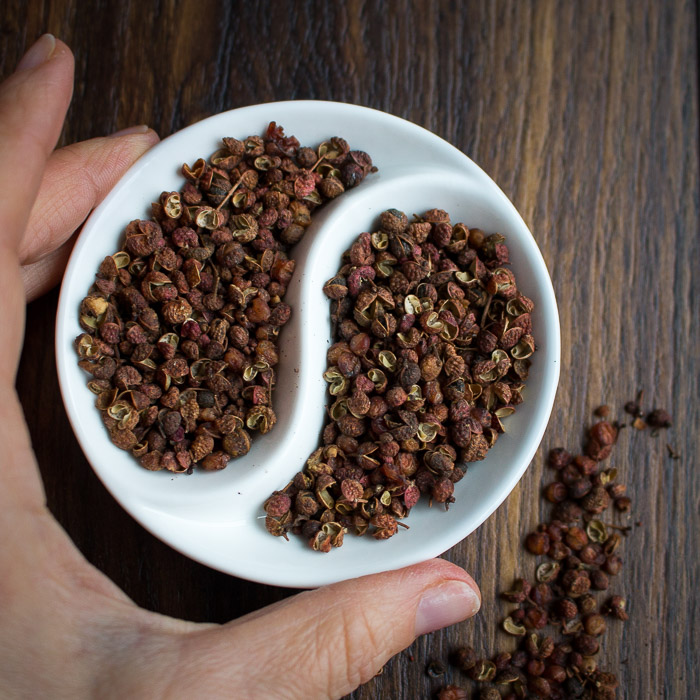 Dried Sichuan peppercorns in a white yin and yang bowl.