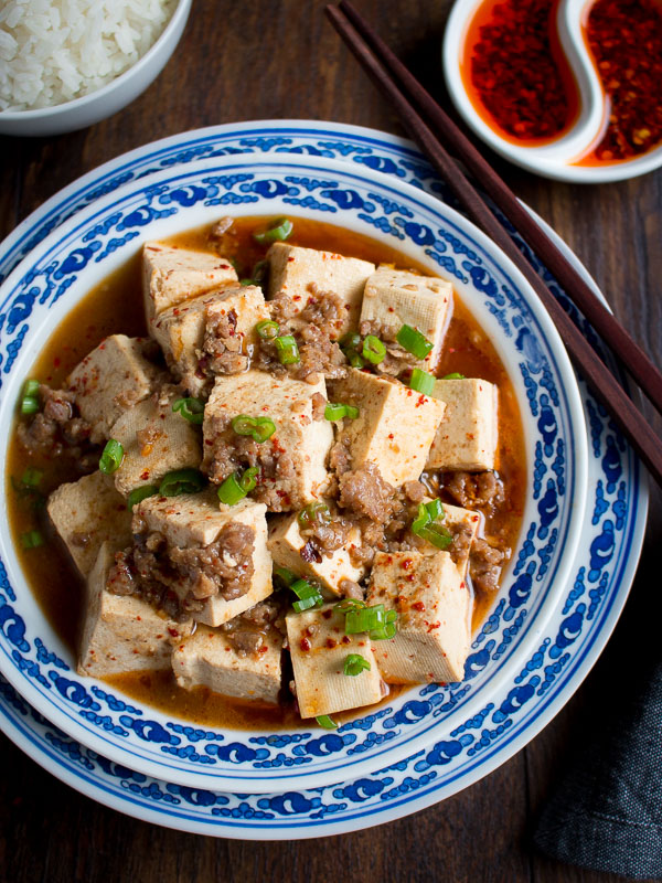 Close up of mapo tofu really showing the chili spices and little bits of pork and green onions.