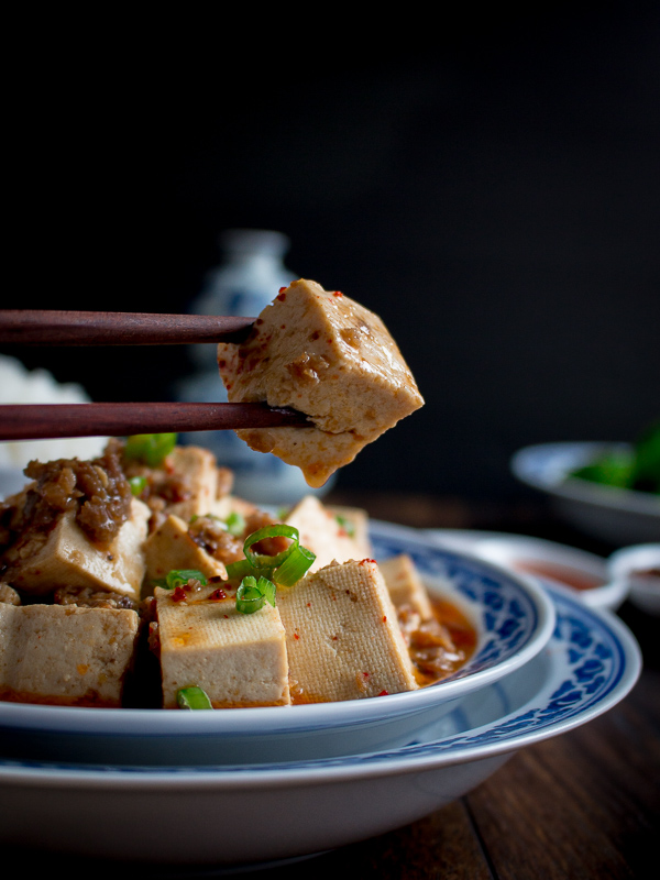Chili covered tofu cube held by wooden chopsticks.