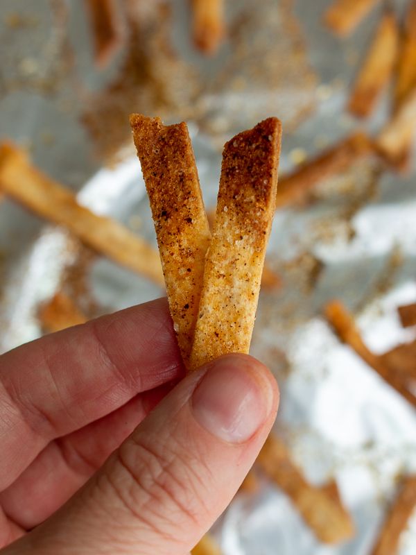 Hand holding up over the baking sheet 2 perfectly crispy baked tortilla strips.