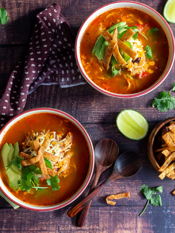 Two bowls of chicken tortilla soup with a lime and bowl of crispy tortilla strips