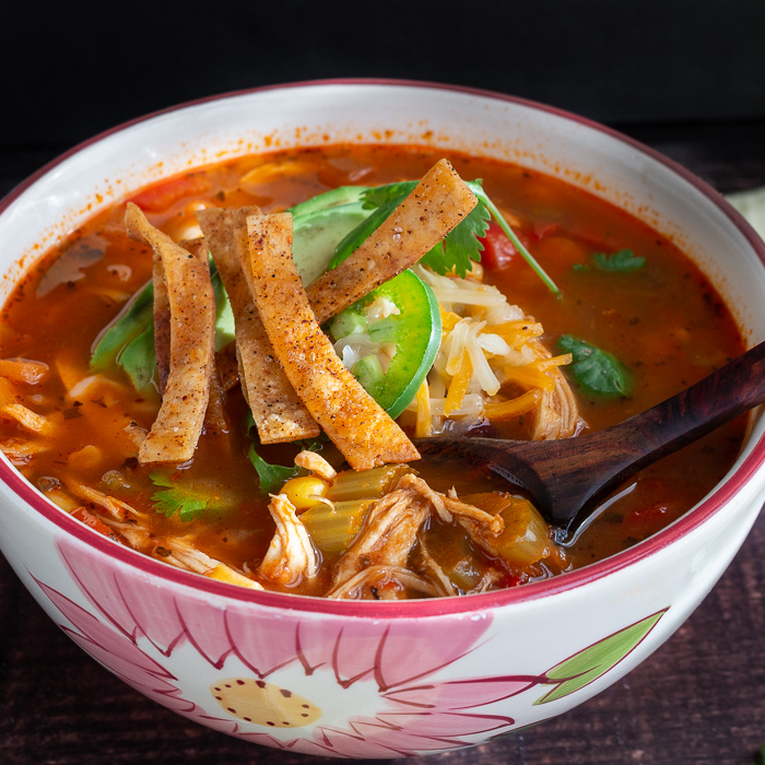 Bowl of Chicken Tortilla soup topped with baked tortilla strip with a wooden spoon grabbing a bite.