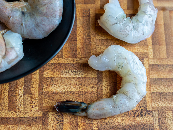 Raw shrimps getting peeled.