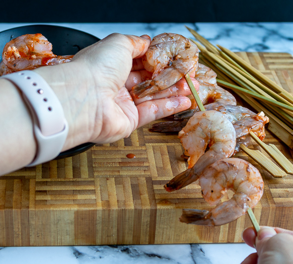 Marinated shrimp being placed on the skewer sticks.