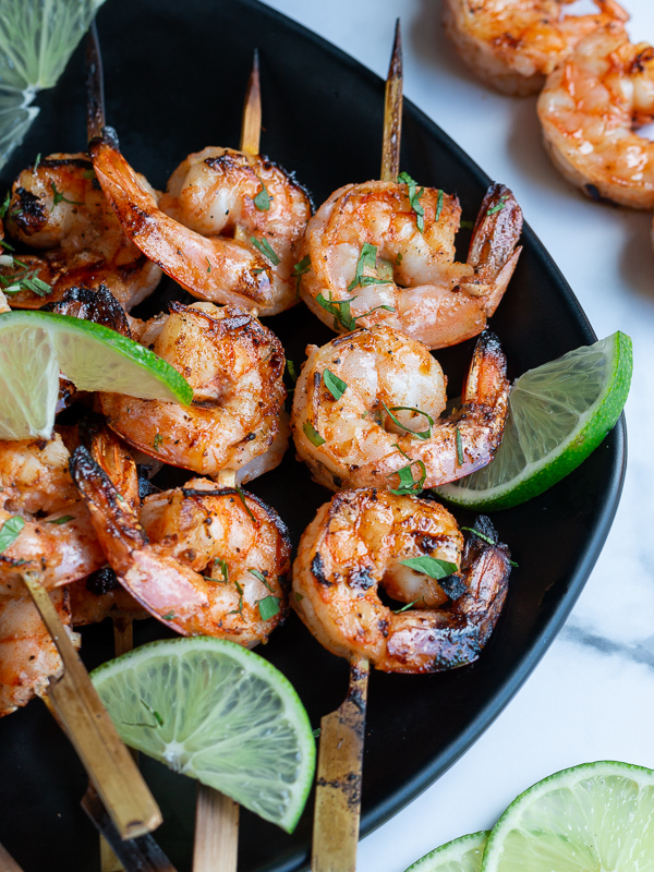Firecracker grilled shrimp just off the grill garlished with lime and cilantro on a black plate and marble table.