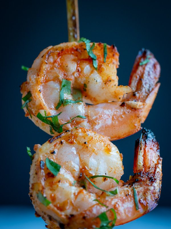 One shrimp skewer held in the air, cooked with 2 perfectly cooked shrimps with cilantro garnish. Super closeup.