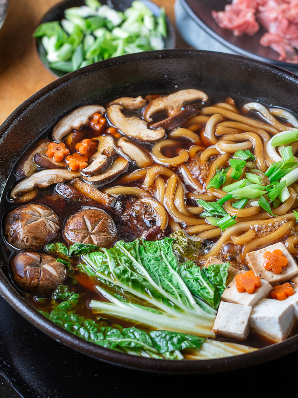Sukiyaki Beef Udon with all the ingredients cooking in a black iron pot.