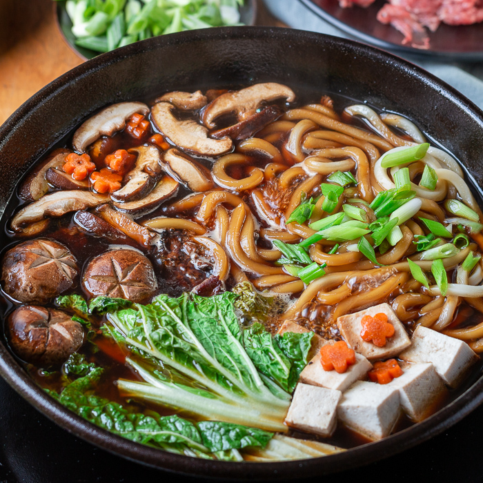 Pot of cooking sukiyaki on the table with ready to eat beef, mushrooms, udon, tofu and napa cabbage decorated with carrot flower slices.