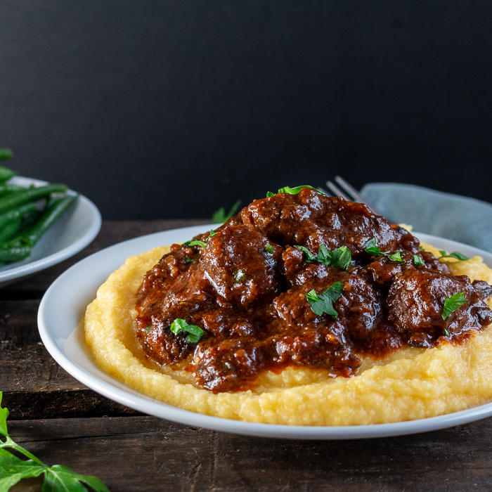 Tuscan Slow Cooked Braised Beef in Wine Sauce on a bed of polenta, garnished with parsley and a side of green beans. Super saucy and tender.
