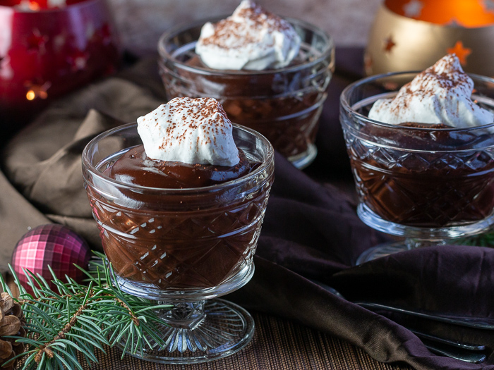 3 cups of chocolate pudding in glass dishes with a dollop of coconut whipped topping and a holiday scene.