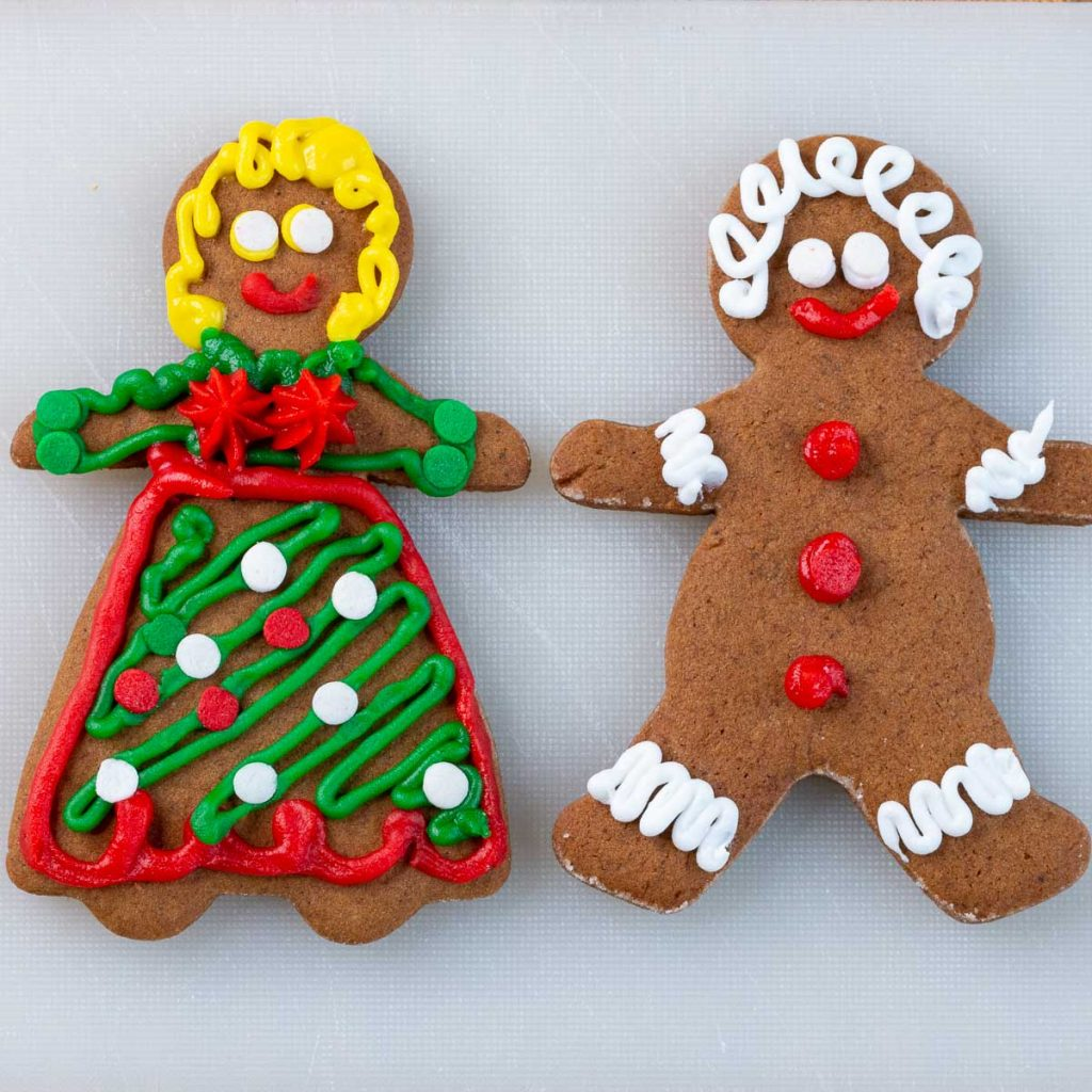 Decorated gingerbread man and gingerbread women on a white cutting board.