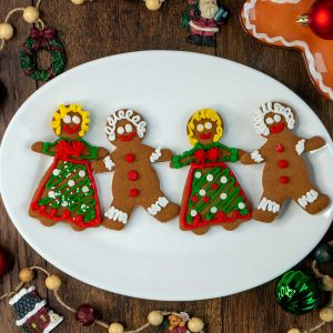 4 adorable gingerbread men and women on a white plate all holding hands.