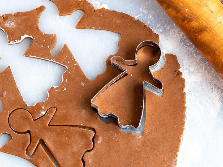 Gingerbread women getting cut out of dough.