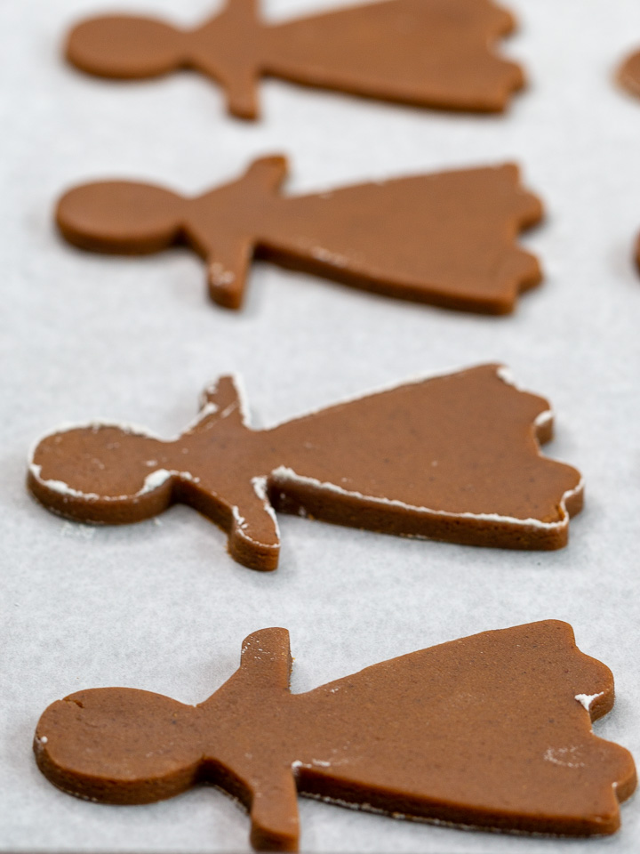 4 gingerbread women on lined baking sheet with parment paper ready to be baked.