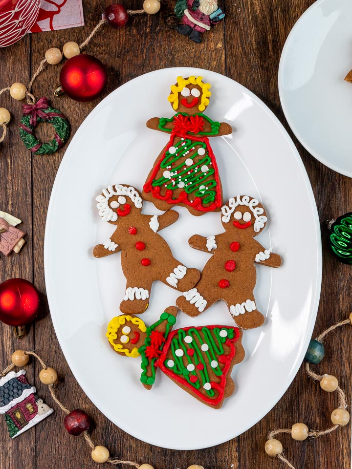 4 decorated gingerbread men and women on a white plate with holiday decorations around the plate.