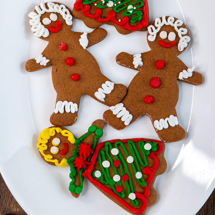 4 cute little decorated homemade gingerbread cookies on a plate.