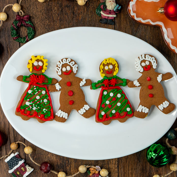 Homemade gingerbread cookies all decorated men and women holding hands on a white plate.