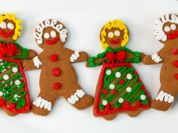 4 decorated cut out molasses cookies holding hands.