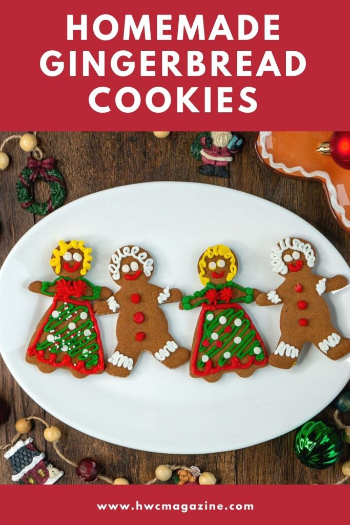 Homemade Gingerbread Cookies decorated with royal icing on a white plate all holding hands.