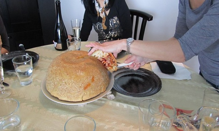 Timpano Italian Pasta Dome getting cut into at the dinner table