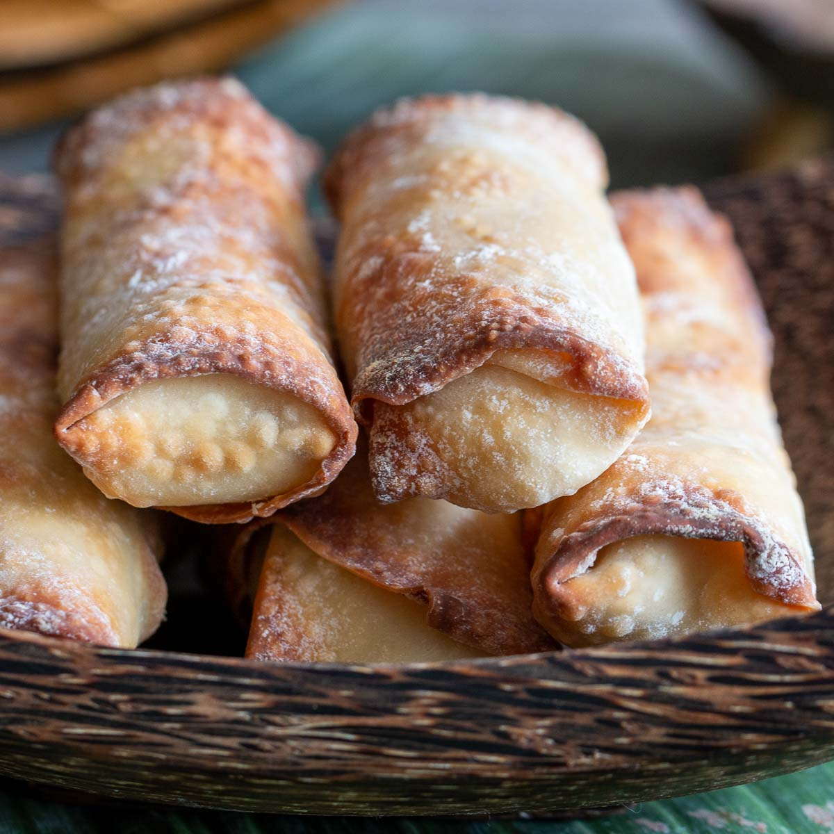 Stack of air fried spring rolls in wooden bowl.