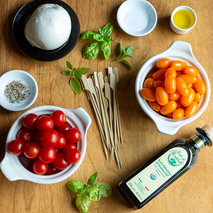 Ingredients of fresh mozzarella, cherry tomatoes, balsamic, EVOO and skewers on a wooden board.