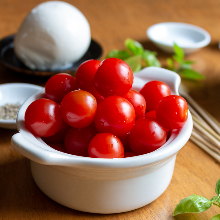 Red Cherry Tomatoes in a white bowl with basil garnish on the side.