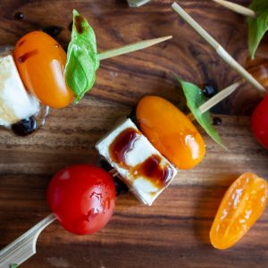 Caprese Salad on a stick drizzled with balsamic glaze.