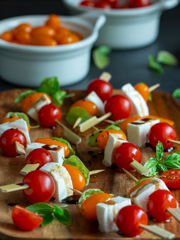 Caprese appetizers on a wooden plate.