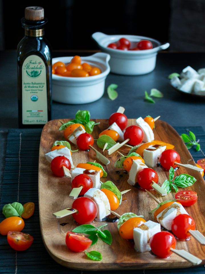 Caprese Skewers on a stick ready to eat with a bottle of balsamic vinegar in the background.