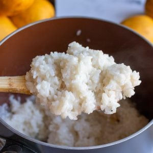 Spoonful of cooked sticky rice over the pot.