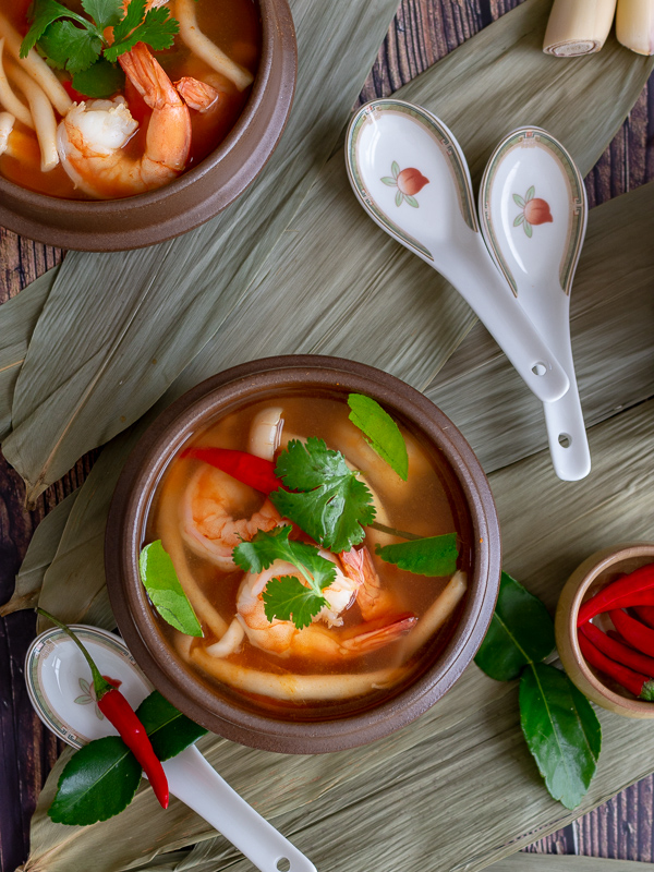 Two Tom yum goong soup bowls laid on top of bamboo leaves with fresh chilis, kaffir lime leaves and lemon grass around.