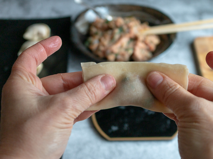Folding the wonton in half and getting the air out around the filling.