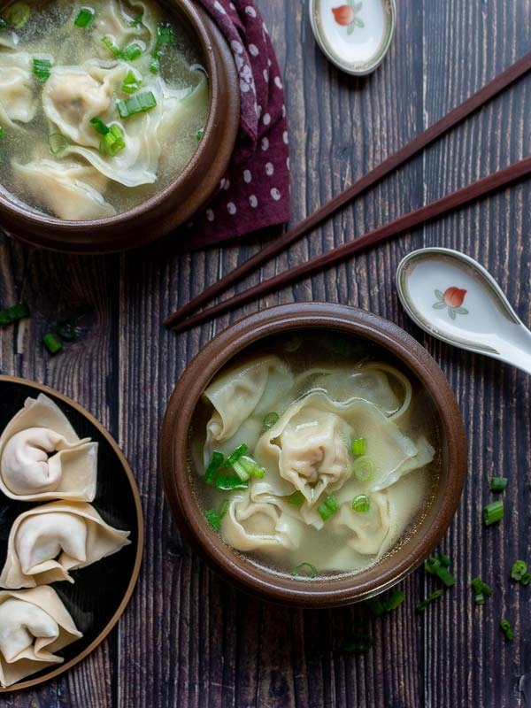 Two bowls of wontons soup, prepared wontons, chopsticks and a spoon, ready to eat.