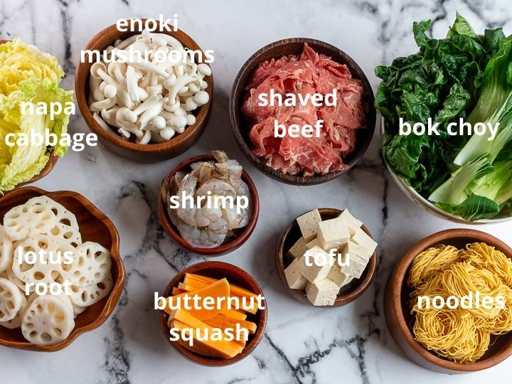Mushrooms, beef, green leafy vegetables, tofu, and lotus root in wooden bowls.
