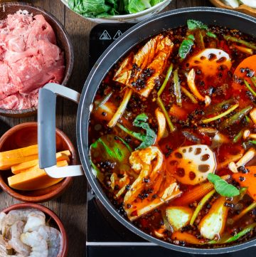 Spicy Sichuan Hot Pot cooking with vegetables and beef and other vegetables around the hot pot in bowls.