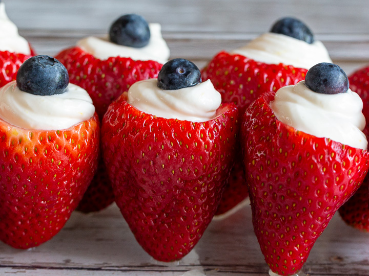 Red, white and blue strawberries are lined up in a row in the refrigerator.